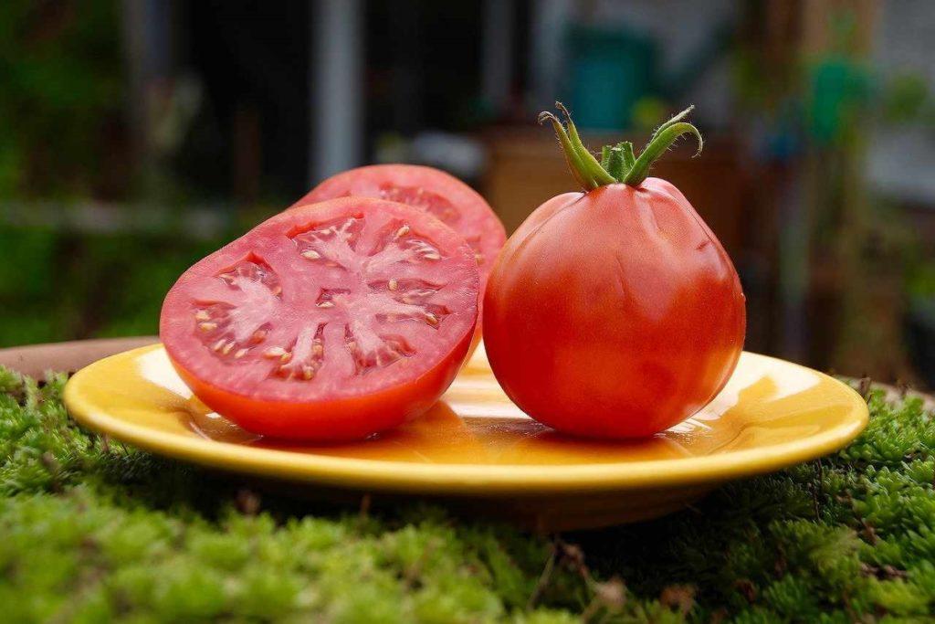 切ってないトマトと半分に切ったトマトが皿の上に置いてある